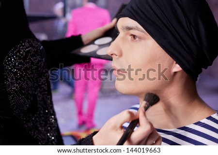 Making-up of young actor before shooting him in new clip - stock photo