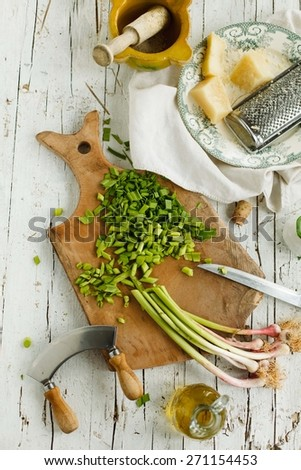 Making young garlic pesto with cheese over vintage cutting board. Rustic style.  - stock photo