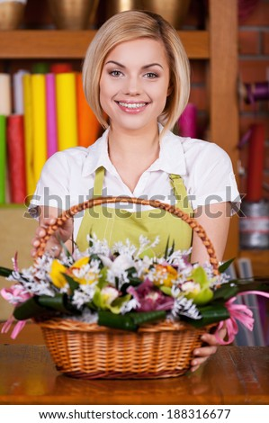 Making your life colored. Attractive young blond hair woman in apron stretching out basket full of flowers and smiling - stock photo