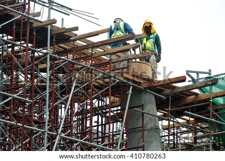 MALACCA, MALAYSIA -MARCH 25, 2016: Construction workers fabricating beam and column timber form work and reinforcement bar at the construction site in Malacca, Malaysia. - stock photo