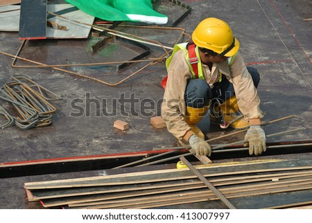 MALACCA, MALAYSIA -MARCH 29, 2016: Construction workers fabricating steel reinforcement bar at the construction site in Malacca, Malaysia. The reinforcement bar was ties together using tiny wire.    - stock photo