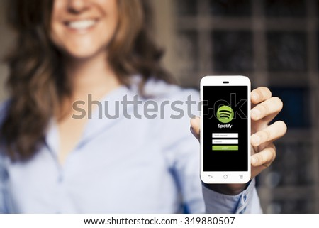 MALAGA, SPAIN - APRIL 26, 2015: Smiling woman holding a mobile phone with Spotify App in the screen. - stock photo