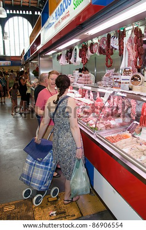 MALAGA, SPAIN - JUNE 10: Unidentified sellers pack meat at their shop in the popular central market on June 10, 2011 in Malaga, Spain. It was renovated in 2010 and it was reopened on March 2011. - stock photo