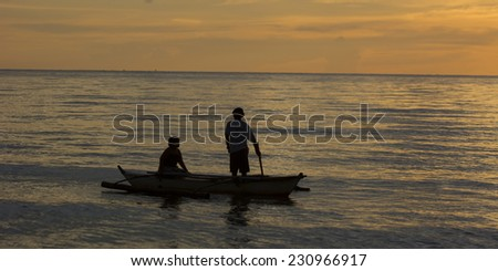 Malandog, Philippines - November 15, 2014: Two persons fishing from an small outrigger during sunset - stock photo