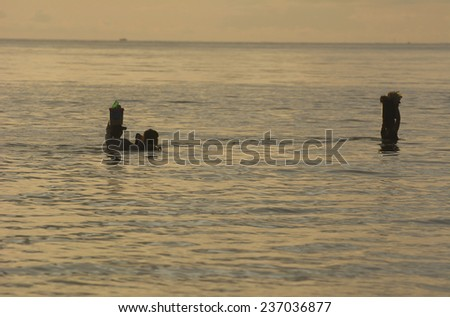 Malandog, Philippines - October 20, 2014: People walking in shallow water to cross a river - stock photo
