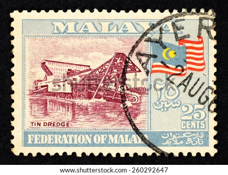 MALAYA - CIRCA 1960: Blue color postage stamp printed in Federation of Malaya with illustrative image of a tin dredge machine and Federation of Malaya flag. - stock photo