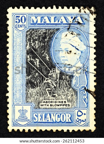 MALAYA - CIRCA 1957: Blue color postage stamp printed in Selangor (Federation of Malaya) with illustrative image of aborigines with blowpipes and  portrait of Sultan Sir Hishamuddin Alam Shah Al-Haj. - stock photo