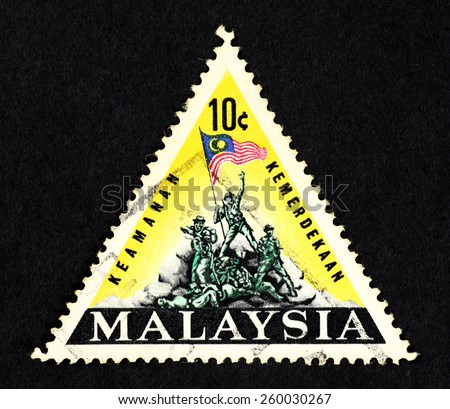 MALAYA - CIRCA 1966: Yellow color triangle shaped postage stamp printed in Malaysia with illustrative image of the Malaysian national monument (Tugu Negara).  - stock photo
