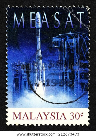 MALAYSIA - CIRCA 1996: Blue color postage stamp printed in Malaysia with image of a space rocket on a launchpad to commemorate Malaysia's first satellite communications system. - stock photo