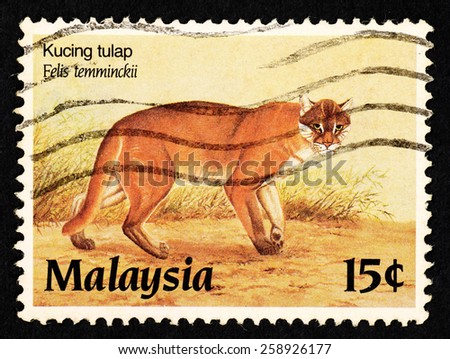 MALAYSIA - CIRCA 1987: Brown color postage stamp printed in Malaysia with image of an Asiatic golden cat (Felis temminckii) for the Protected Wildlife of Malaysia Series III. - stock photo