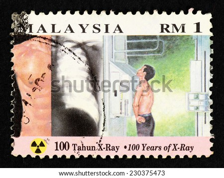 MALAYSIA - CIRCA 1995: Postage stamp printed in Malaysia with image of a man with an X-ray machine to commemorate 100 years of X-ray. - stock photo