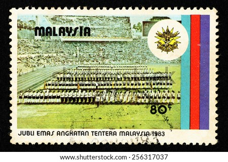 MALAYSIA - CIRCA 1983: Postage stamp printed in Malaysia with image of military parade in a stadium to commemorate the golden jubilee of the Malaysian Armed Force. - stock photo