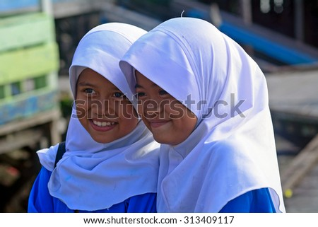 MALAYSIA - MARCH 2 : Muslim schoolgirls in a village on 2 March 2015 in Malaysia, Borneo. Islam has spread out in tribal  Borneo as well.  - stock photo