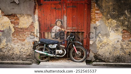 MALAYSIA, PENANG, GEORGETOWN - CIRCA JUL 2014: Public art piece in Malaysia employs multiple media including sculpture and painting for this mural depiction of a boy on a motorcycle. - stock photo