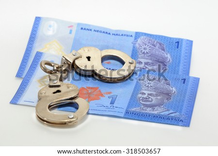 Malaysian banknotes and shackle - stock photo