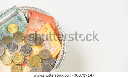 Malaysian cash notes and coins inside aluminium loaf pan with transparent cover. Concept of money eating and saving. Isolated on empty background. Slightly de-focused and close-up shot. Copy space. - stock photo