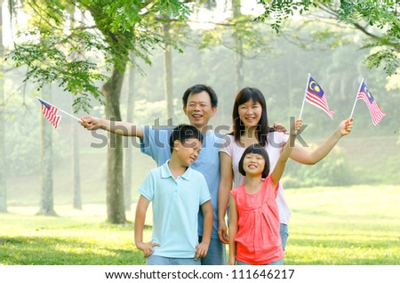 malaysian family raising malaysian flags - stock photo