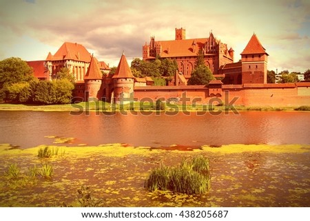 Malbork castle in Pomerania region of Poland. UNESCO World Heritage Site. Teutonic Knights' fortress also known as Marienburg. Nogat river. Vintage filtered color tone. - stock photo
