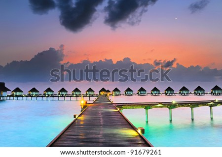 Maldives bungalows sunset - stock photo