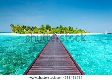 Maldives. Island in the ocean. Palm trees on the white sand beach. Turquoise water of the lagoon.  - stock photo