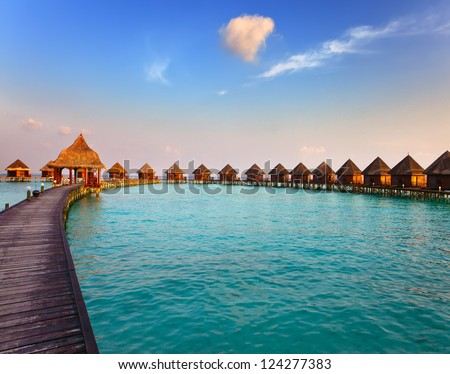 Maldives.  Villa on piles on water at the time sunset. - stock photo