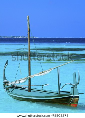 Maldivian Dhoni anchored in shallow bay - stock photo