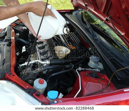 Male adding oil with a funnel from the left side of a red car after a do-it-yourself oil change. Dipstick is nearby. - stock photo