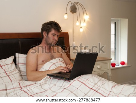 male adult Working from home in bed - stock photo