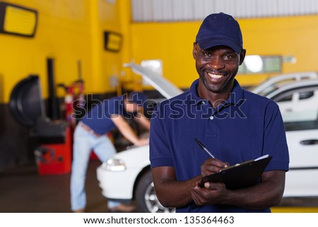 male african american vehicle mechanic writing report - stock photo