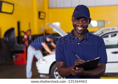 male african american vehicle mechanic writing report - stock photo