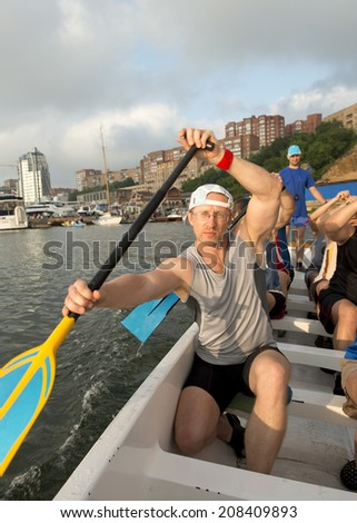 """Male amateur rowing in boats """"Dragon"""" in training, Vladivostok, Russia - stock photo"""
