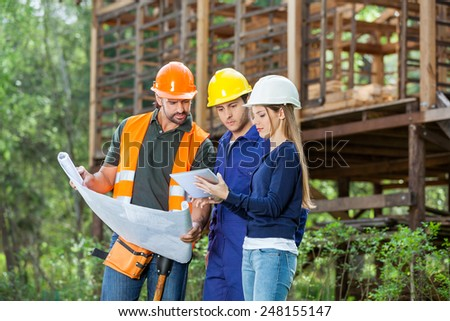 Male and female architects using digital tablet while reviewing blueprint at construction site - stock photo