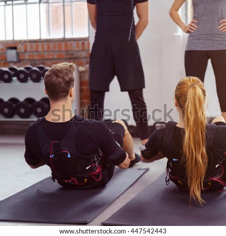 Male and female athletes being supervised as they exercise in a ems fitness studio on yoga mats - stock photo