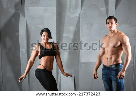 Male and female bodybuilders. Fitness, sport, training, gym and lifestyle concept - two smiling people standing in the gym. The idea of article about sport and fitness. - stock photo