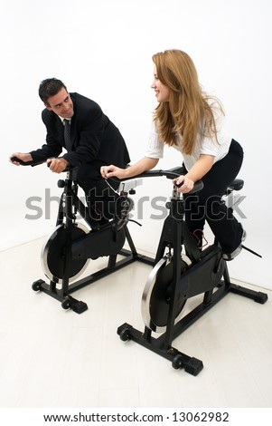 Male and female business colleagues looking at each other and smiling while working out on exercise bikes. Vertical shot isolated against a studio background. - stock photo