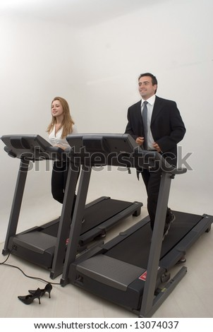 Male and female business colleagues on a treadmill together. Isolated against a studio background - stock photo