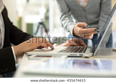 Male and Female Businesspeople discussing Project at Computer in modern Office Loft environment at grey Table with Electronics and Stationery - stock photo