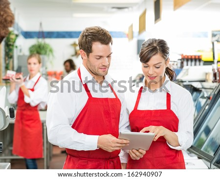 Male and female butchers using digital tablet at store with colleagues working in background - stock photo