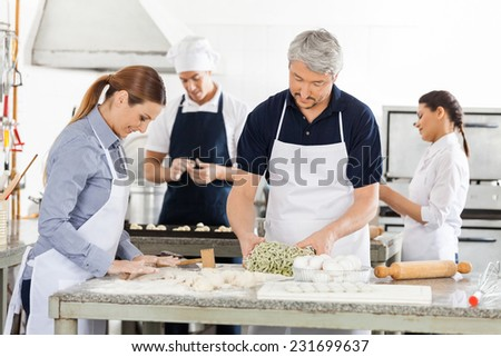Male and female chefs preparing pasta together in commercial kitchen - stock photo
