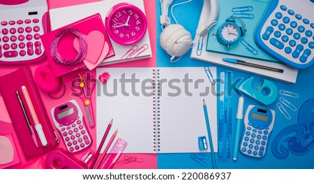 Male and female desktop with cyan and pink stationery and open notebook. - stock photo