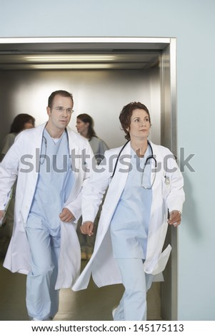 Male and female doctors running out of elevator - stock photo