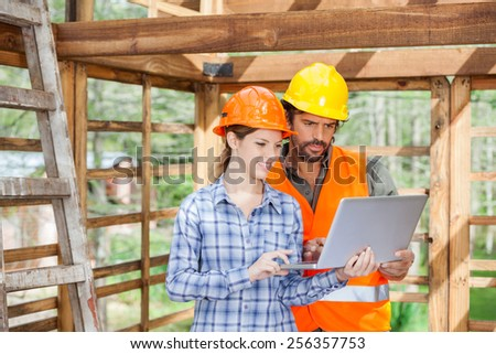 Male and female engineers working on laptop together at construction site - stock photo