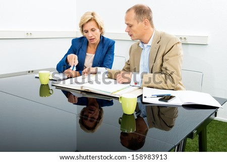 Male and female environmentalists discussing over documents at desk in office - stock photo