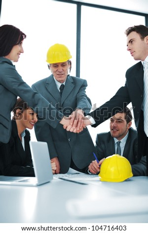 Male and female executives shaking hands in front of colleagues - stock photo