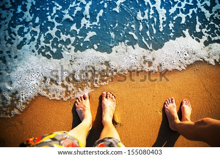 Male and female feet are standing on the sandy beach - stock photo