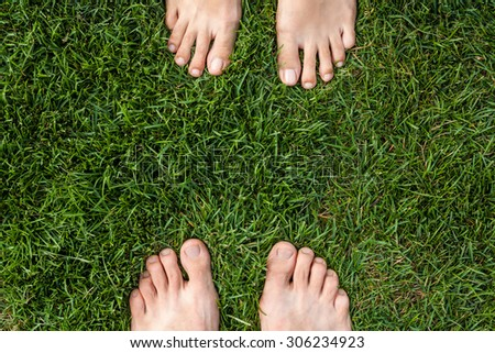 Male and female feet over green grass - stock photo