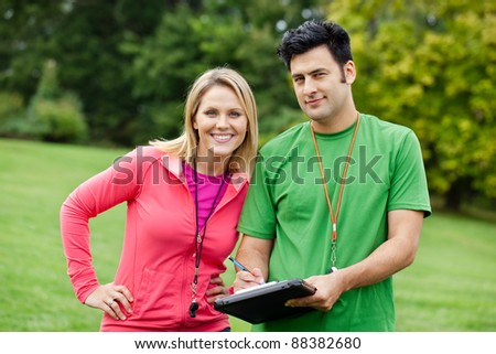 Male and female fitness trainers holding a clipboard - stock photo
