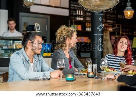 Male and female friends conversing while having food at restaurant - stock photo