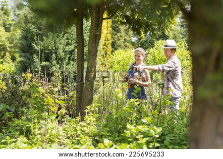 Male and female gardeners discussing over plants at plant nursery - stock photo