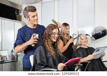 Male and female hairdressers setting up client's hair in beauty salon - stock photo